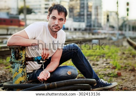 Handsome young man in white t-shirt sitting on the ground near the water fountain against the  railroad station background. Image with selective focus - stock photo