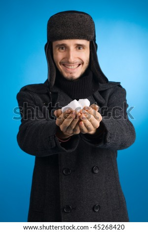 Handsome young man in winter clothing holding out a handful of snow