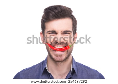 Handsome young man is holding chili pepper in his teeth while standing against white background. - stock photo