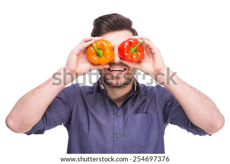 Handsome young man is holding salad peppers in front of his eyes while standing against white background. - stock photo