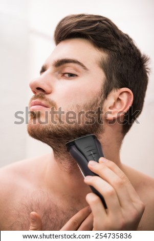 Handsome young man is shaving with electric razor while looking at the mirror.