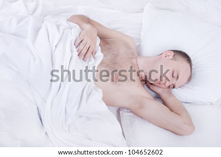 handsome young man is sleeping in bed with white linen - stock photo