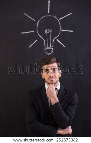 Handsome young man is standing against blackboard with chalk drawing of light bulb.