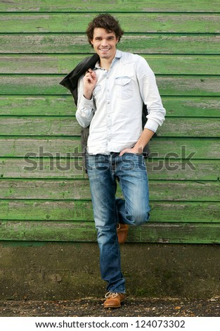 Handsome young man leaning against a green wooden wall outdoor. He is holding his jacket and hand in pocket. One leg up - stock photo