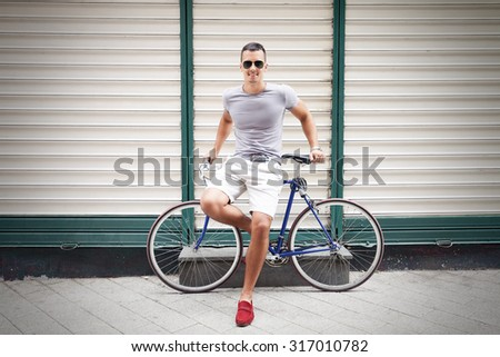 Handsome young man leaning on his bicycle and smiling to camera - stock photo