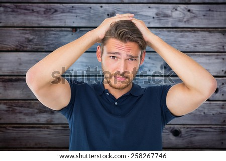Handsome young man looking confused against grey wooden planks - stock photo