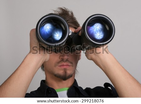 Handsome young man looking through a binoculars. Portrait of young man with binoculars against a gray wall. Looking for new opportunities. Confident young man in shirt looking through binoculars. - stock photo