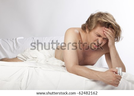 Handsome young man lying in bed with a terrible headache. Studio image. See more in my portfolio - stock photo