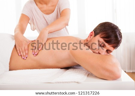 Handsome young man lying on his stomach in a spa having a back massage - stock photo