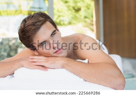 Handsome young man lying on massage table at spa center - stock photo