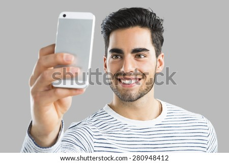Handsome young man making a selfie picture with phone, isolated over gray background - stock photo