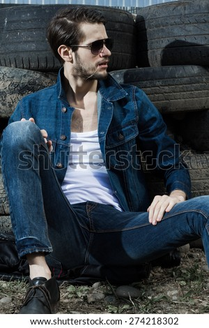 Handsome young man near car tires. - stock photo