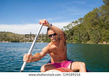 Handsome young man on a canoe on a lake, paddling, enjoying a lovely summer day - stock photo