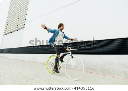 Handsome young man on bike without hands in the city. Bicycle concept - stock photo