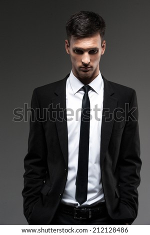 Handsome young man on grey background. front view of man in unbuttoned suit looking into camera  - stock photo
