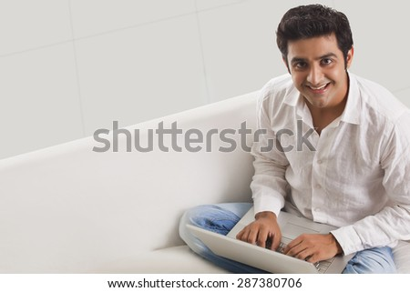 Handsome young man on sofa using laptop