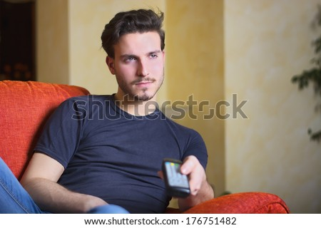 Handsome young man on sofa, using TV remote control and looking off camera. Indoors shot - stock photo