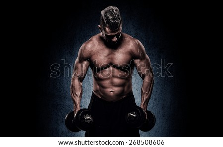handsome young man on wall background doing exercises for the biceps - stock photo