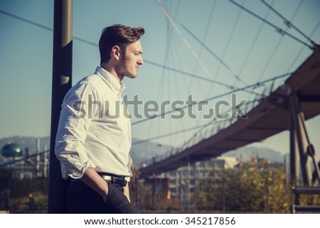 Handsome young man outside wearing white shirt, looking to a side. Profile view, day shot. - stock photo