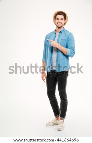 Handsome young man pointing away and smiling while standing against white background - stock photo