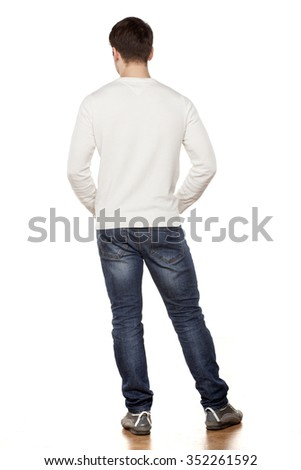 handsome young man posing in jeans from the back - stock photo