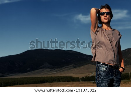 Handsome young man posing over picturesque landscape. - stock photo