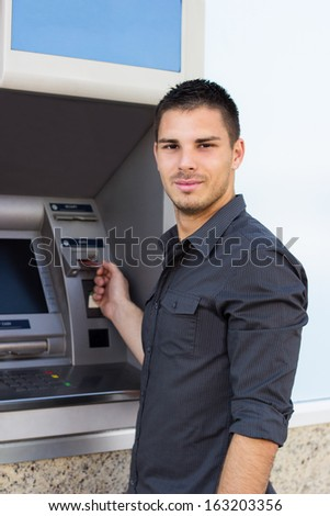 Handsome young man put his credit card at the ATM  - stock photo