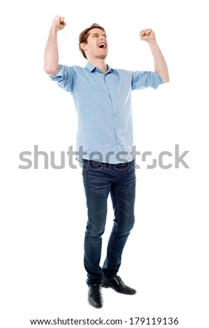 Handsome young man raising his arms in excitement - stock photo