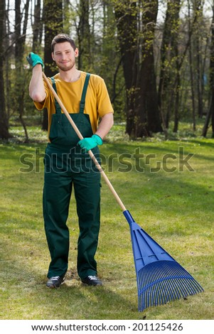 Handsome young man raking leaves in garden - stock photo