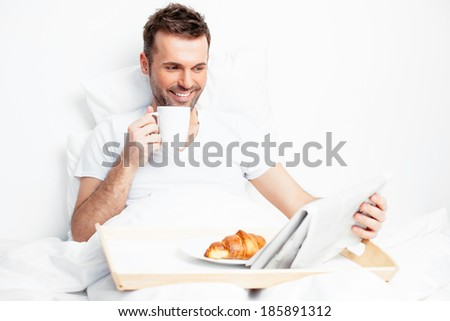 Handsome young man reading a morning paper in bed - stock photo