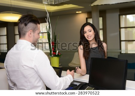 handsome young man receptionist handing over room keys to a beautiful woman in hotel front desk