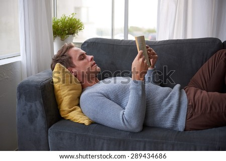 Handsome young man relaxing on his couch and comfortably reading a book