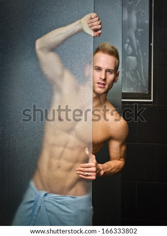 Handsome young man shirtless with towel around waist - stock photo