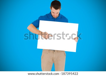 Handsome young man showing card against blue background with vignette - stock photo