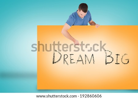 Handsome young man showing card with dream big against blue background - stock photo