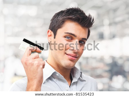 Handsome young man showing his credit card - stock photo
