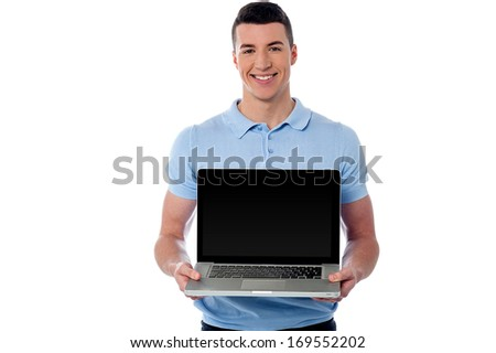 Handsome young man showing his new laptop