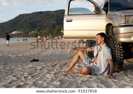 handsome young man sit near wheel on the sand beach of Phuket - stock photo