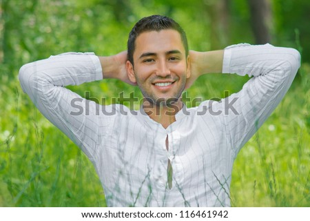 Handsome young man siting on meadow -SMALL DOF - stock photo