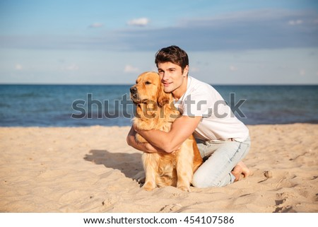 Handsome young man sitting and hugging his dog on the beach - stock photo