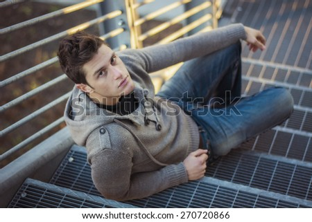Handsome young man, sitting and leaning on metal grid stairs outdoors, looking at camera - stock photo