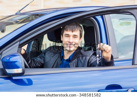 Handsome young man sitting in his new car with car key