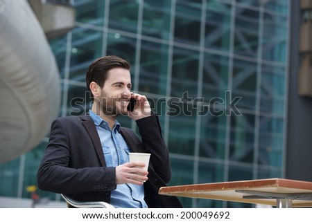 Handsome young man sitting in the city with mobile phone and coffee - stock photo