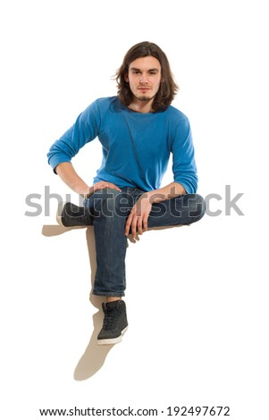 Handsome young man sitting on a banner with legs crossed. Full length studio shot isolated on white. - stock photo