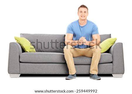 Handsome young man sitting on a modern sofa isolated on white background - stock photo