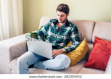 Handsome young man sitting on couch working on his laptop - stock photo