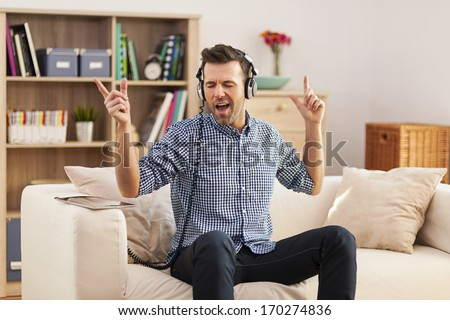 Handsome young man sitting on his sofa and listening to music   - stock photo