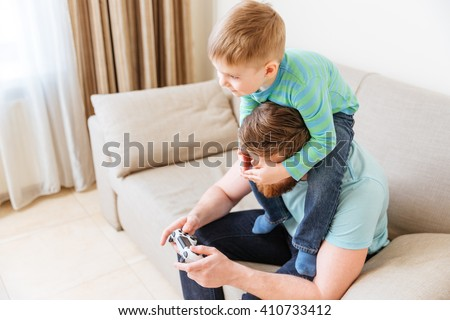 Handsome young man sitting on sofa and playing computer games while his little son covering his eyes - stock photo