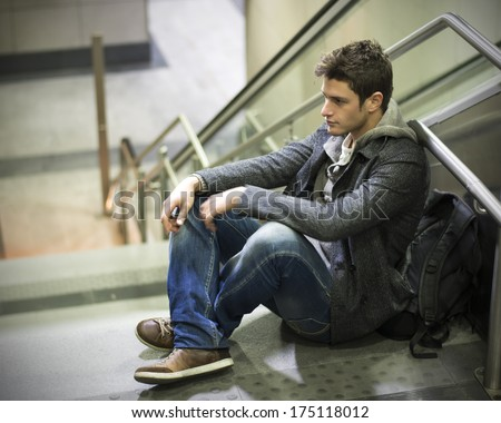 Handsome young man sitting on stairs' marble steps, backpack behind him - stock photo