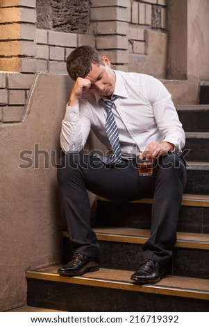 Handsome young man sitting on stairs. portrait of guy drinking whisky and sleeping - stock photo